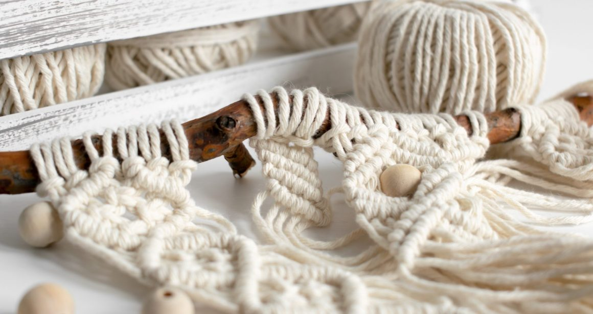 Eine junge Frau knüpft einen Makramee Wandbehang. Im Online Workshop die Grundlagen des Makramees lernen.